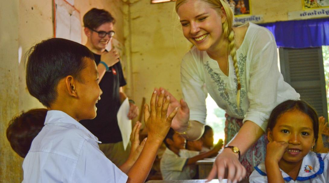 A teenage volunteer working with children in Cambodia gives a young child a high-five in the classroom.